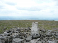 The trig point of Cross Fell with the misty haze of the Eden Valley to the west